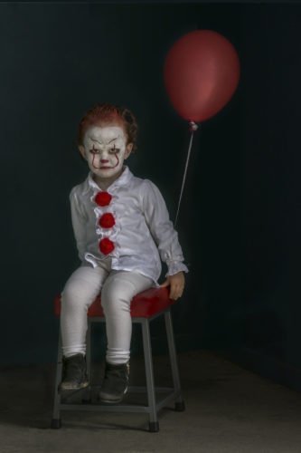 A low key photograph of a young girl dressed as a clown