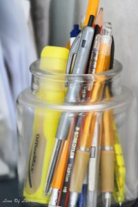 A photo of pens in a jar taken in a very dark environment at ISO 6400