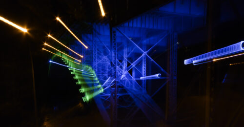 Abstract photo of Hamilton bridge at night showing the blue, green and yellow street lighting in streaks