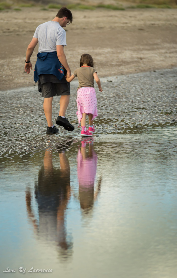 A photo of a man and his daughter reflected in a puddle as they stroll along the beach.