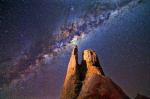 A photograph of the milky way with huge rocks composition in foreground highlighted with light painting