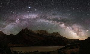 A photograph of the milky way with mountains as the horizon to emphasise how immense the galaxy is