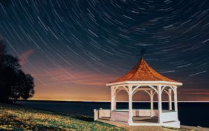 A photograph of star trails with a light painted pavilion in foreground to add interest to the image