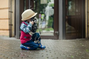 A humorous image of a very young photographer wearing a hat to depict the many hats a newborn photographer has to wear.