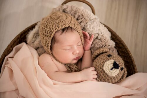 A photo of a gorgeous Newborn by photographed with props consisting of a round basket, flokati throw, brown Teddy Bear and beige wrap and matching cap