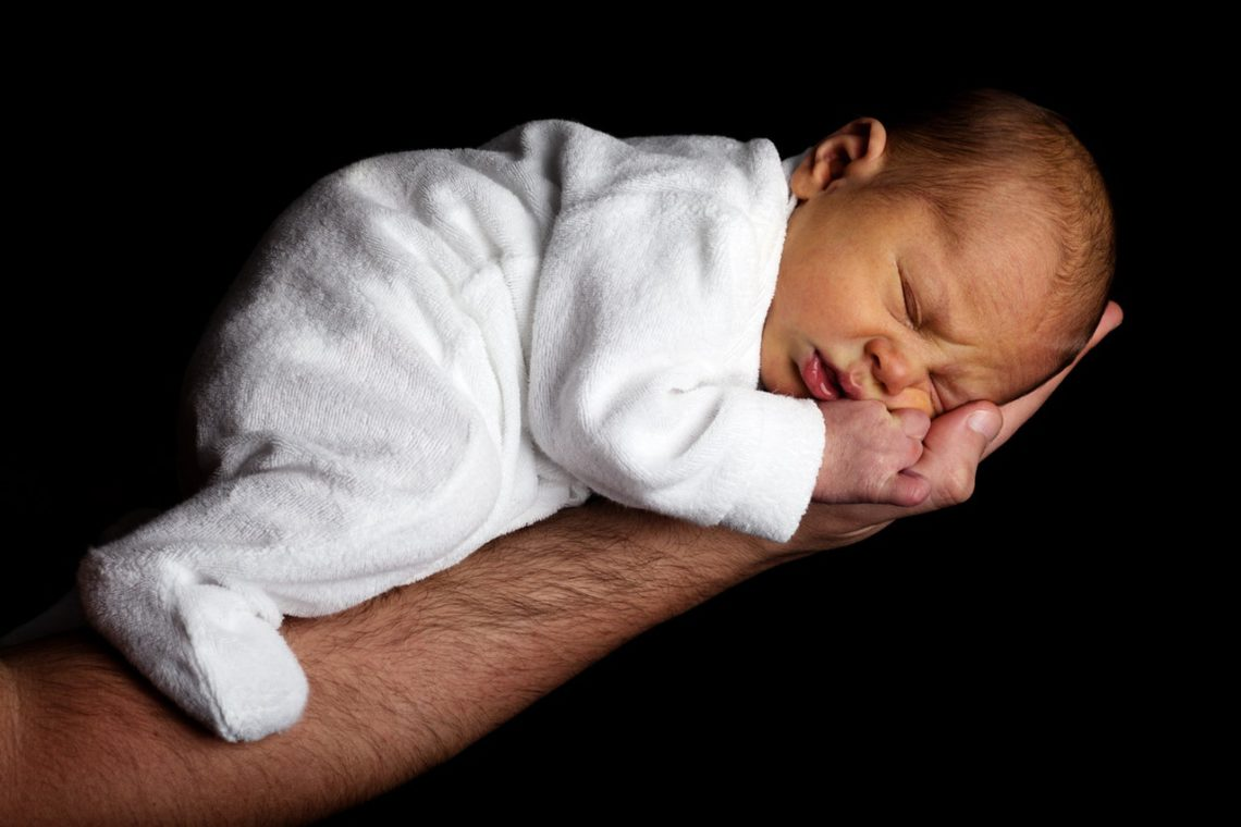 A photo of a newborn baby just a few days old lying asleep on his father's arm
