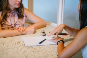 A photo of a photographer going through her contract with a prospective client.