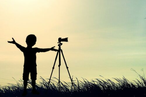 Silhouette of a young photographer with camera mounted on tripod